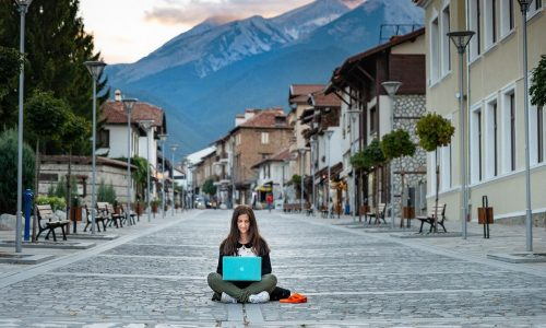 women-digital-nomad-sitting-middle-of-the-street